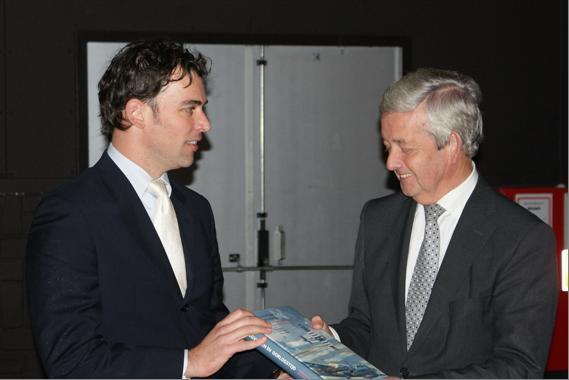 Erwin van Loo viel de eer te beurt de eerste exemplaren uit te mogen reiken, aan de Minister van Defensie Eimert van Middelkoop die het vervolgens triomfantelijk aan de genodigden toont. (@SGLO)