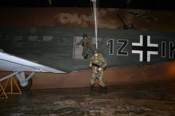 Duitse Fallschirmjager springen uit een Junkers Ju 52 boven een grote kaart van Nederland (SGLO – @P. Righart van Gelder)
