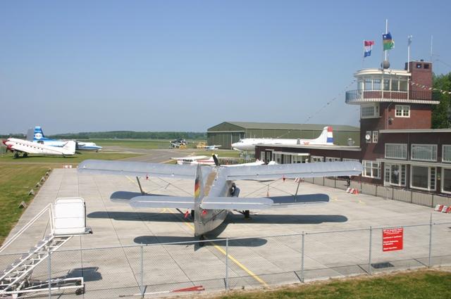 Een Antonov An-2 met rechts het Schiphol gebouw waar de boekendienst zal zijn. Deze foto is uit 2007 en de Dakota is inmiddels in restauratie. (SGLO – @P. Righart van Gelder)