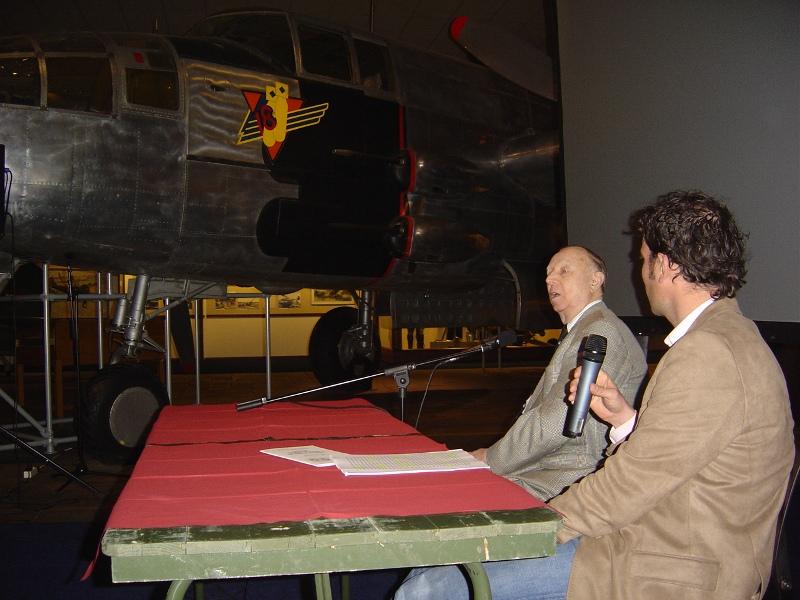 Dhr. Beukhof, boordschutter van 320 Squadron aan het woord met op de achtergrond een B-25 Mitchell, het type waar hij op vloog (SGLO – Archive)