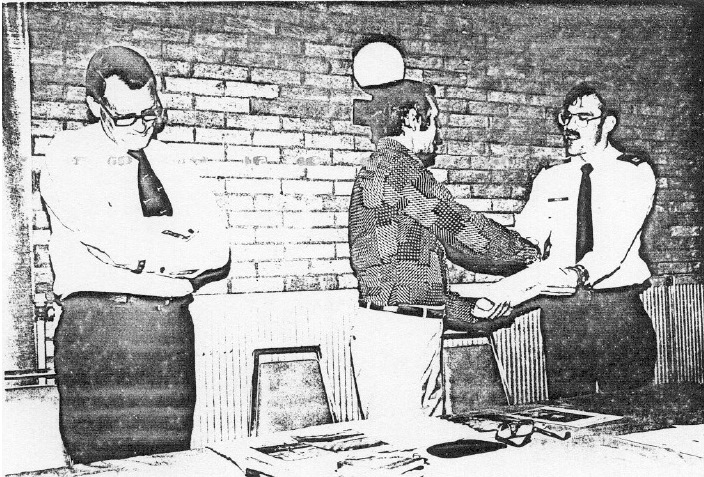Als blijk van waardering voor de goede zorgen krijgt Captain Peck (rechts) een boek over de RAF overhandigd. Links op de foto A.P. de Jong. In het midden Kwik. (SGLO – Archive)