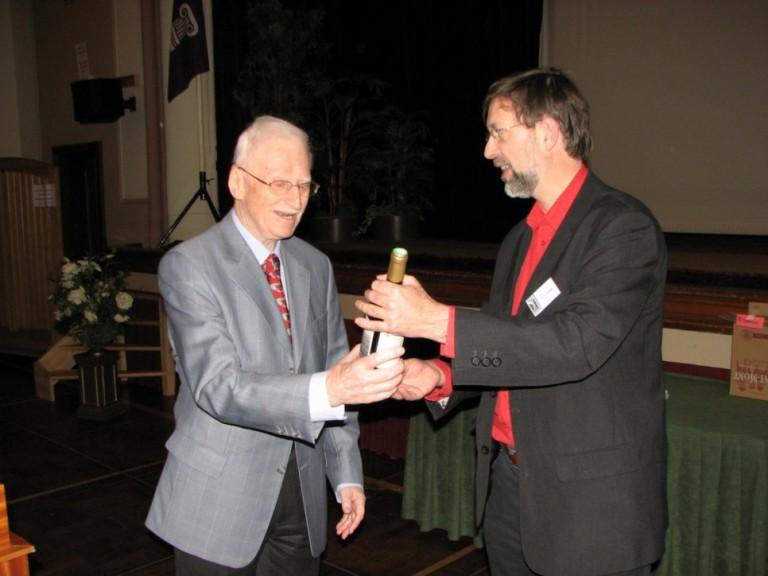 Lt. Ernst Eduart Witt krijgt een fleswijn overhandigd van Peter Grimm als dank voor zijn verhaal (SGLO – Archive)