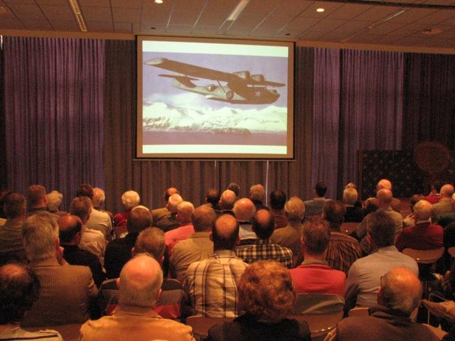 Vol belangstelling keken de aanwezige naar de presentatie over de PH-PBY (SGLO - @H.M. van Sabben)