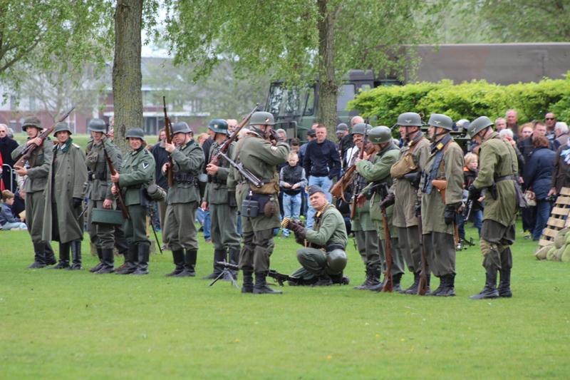 De Duitsers in linie om de hulzen te rapen na afloop.