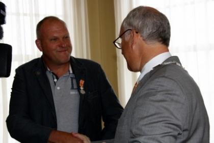 Een stralende Jaap Vermeer ontvangt de felicitaties van burgemeester G. Renkema van Nijkerk. (foto: Nijkerk Nieuws)